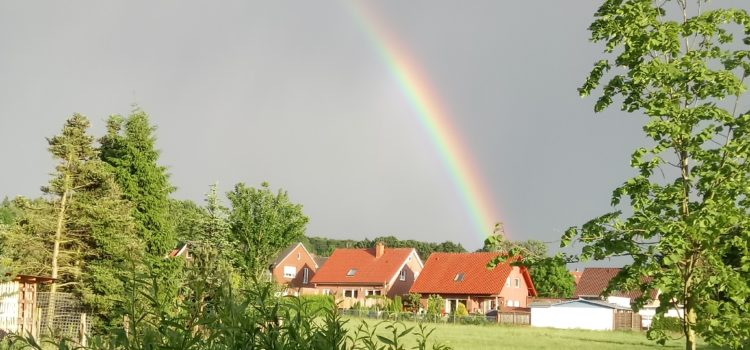 Hannah surft unterm Mai-Regenbogen